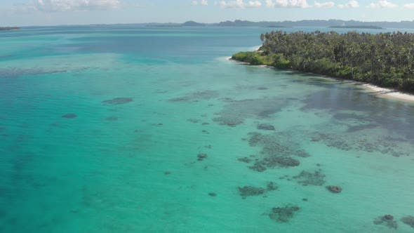 Aerial: flying over exotic white sand beach tropical island secluded destination away from it all