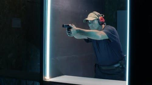 Mature Shooter Firing Pistol in Dark Range