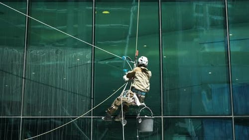 Window Cleaner at Work Washing Office Building Glass Facade