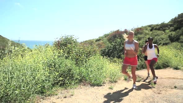 Thumbnail for Three women running outdoors, stopping to catch breath and stretch