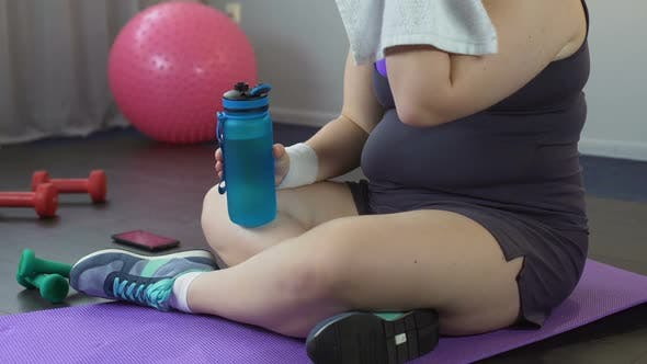 Thumbnail for Plump Lady Restoring Water Balance and Breath After Exhausting Home Workout