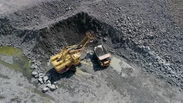 Big Excavator Loading Granite Into Heavy Dump Truck Belaz
