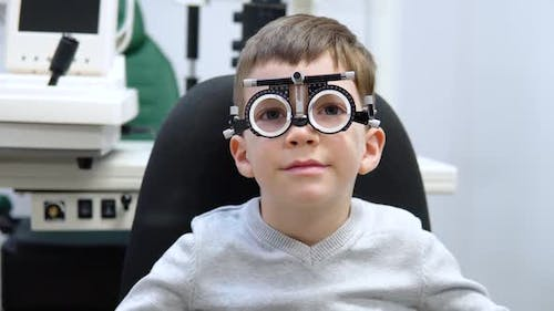 A Boy in a Trial Frame for Lens Selection is Sitting in an Ophthalmology Clinic