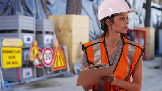 Thumbnail for Construction worker in hardhat and safety vest writing on clipboard at work site