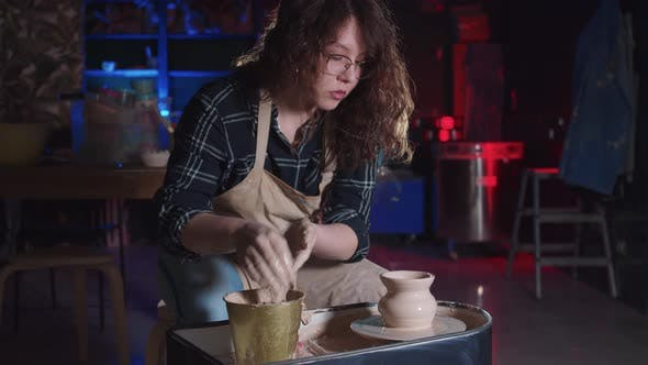 Pottery Crafting  Woman with Curly Hair Making a Simple Pot Out of Wet Clay
