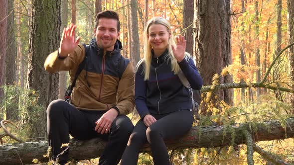 Thumbnail for A Hiking Couple Sits on a Broken Tree in a Forest and Waves at the Camera with a Smile