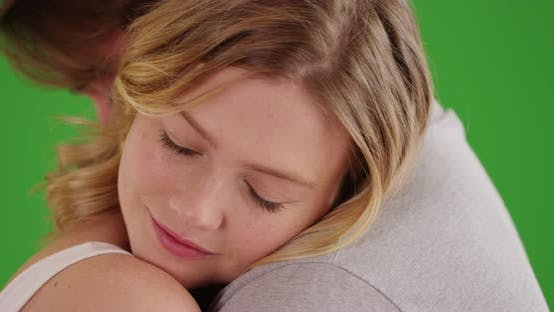 Close up of attractive Caucasian female hugging boyfriend on green screen