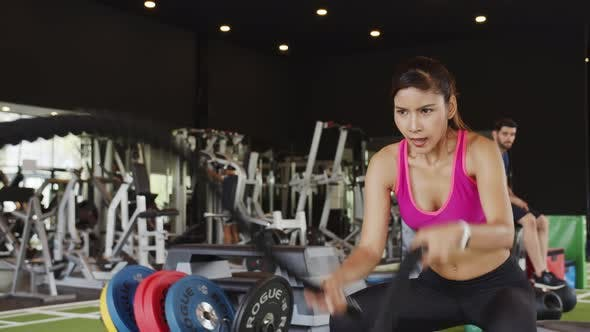 Sporty asian woman working out with battle ropes at gym.