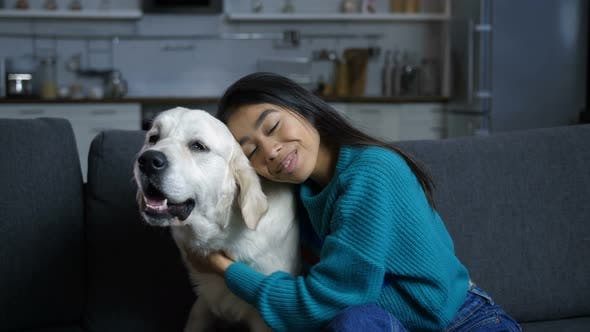 Thumbnail for Young Hindu Woman Petting and Hugging Dog on Sofa