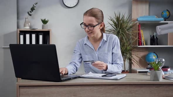 Thumbnail for Young Woman Using Computer and Her Bank Card to Make Online Payment for Purchase