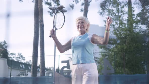Thumbnail for Joyful Mature Woman Won the Tennis Tournament. The Old Lady Jumping Raising Hands Up with the Racket
