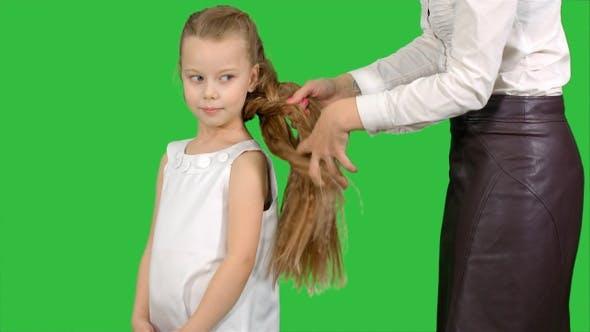Thumbnail for Mutter macht Tochter Frisur auf einem grünen Bildschirm, Chroma Key