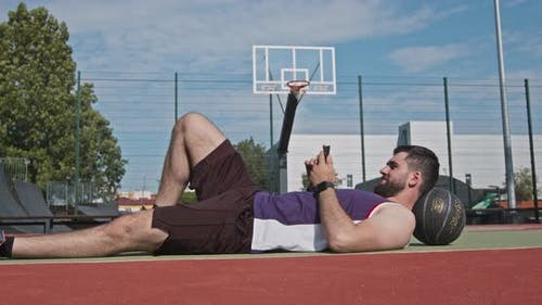 Basketball Player Lying on Floor and Browsing on Smartphone, Outdoor Court Background