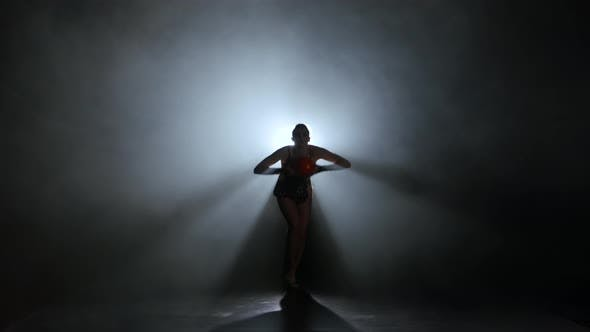 Thumbnail for Gymnast with the Ball Spinning in the Smoke. Light From Behind. Black Background