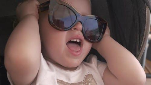 Lovely Baby Girl in Mums Sunglasses