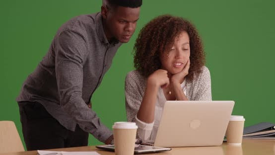 Thumbnail for Black business people working on a laptop while drinking coffee on green screen