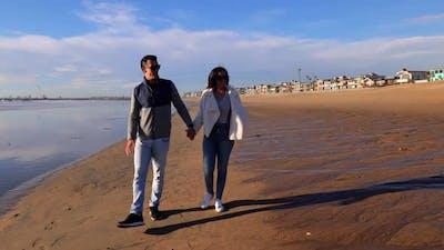 Couple walking their dog on the beach