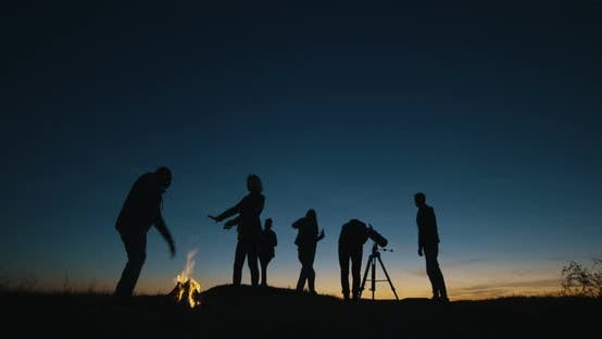 Thumbnail for Friends with Campfire Looking Through Telescope in Night