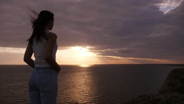 Thumbnail for Slender Girl Standing and Enjoying the Sun Path at the Black Sea in Slo-mo