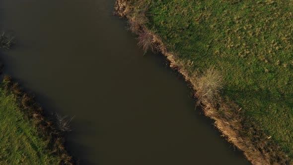 Luftaufnahme - Ein mäandernder Fluss, der eine Agrarlandschaft in Europa zeigt