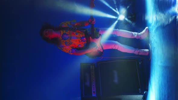 Vertical Video Cheerful Man Jumping Dancing and Playing Guitar in Colored Neon Light Smoke and