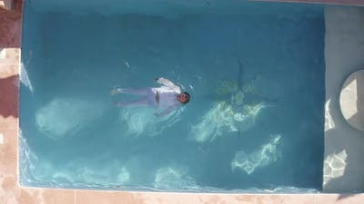 Young Man In White Clothes Swimming In Water