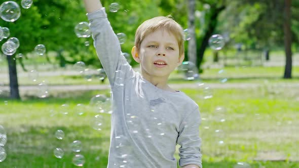 Thumbnail for Happy Boy Making Giant Soap Bubble in Park