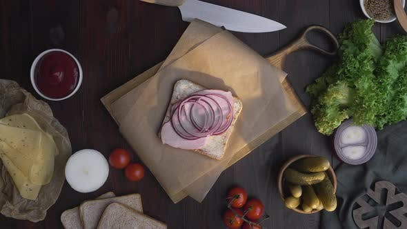 Thumbnail for Flat Lay of Chef's Hand Adds Slised Tomatoes To the Sandwich with Ham and Vegetables on the Wooden