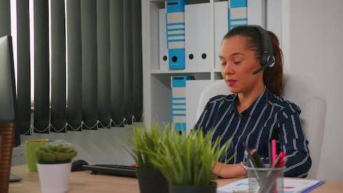 Hispanische Geschäftsfrau mit Headset, die im modernen Büro arbeitet