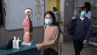 Masked Teen Students Greeting Teacher in Classroom