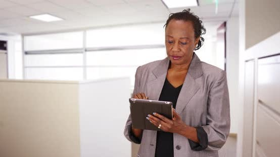 Thumbnail for A black businesswoman using a tablet turns to the camera and says hello
