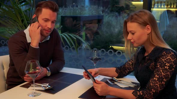 Thumbnail for A Man and a Woman Sit at a Table in a Restaurant, He Talks on a Smartphone, She Works on a Tablet