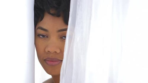 Close up of African American woman behind sheer curtain
