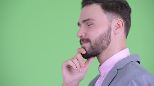 Thumbnail for Closeup Profile View of Happy Young Bearded Businessman Thinking