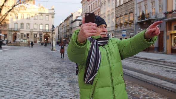 Thumbnail for Senioren-Tourist nimmt Selfie auf und macht Online-Video anrufe mit Smartphone im Winterstadtzentrum