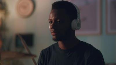 African American Guy Playing Drums in Dark Room