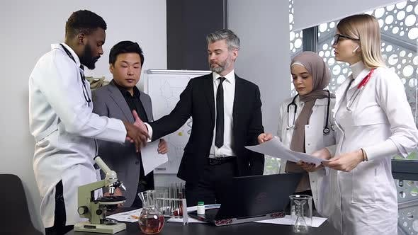 Multi Ethnic Team of Successful Doctors Finishing Clinical Trials on Computer with Handshake