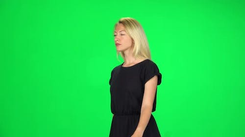 Pensive Girl Is Walking on a Green Screen at Studio.