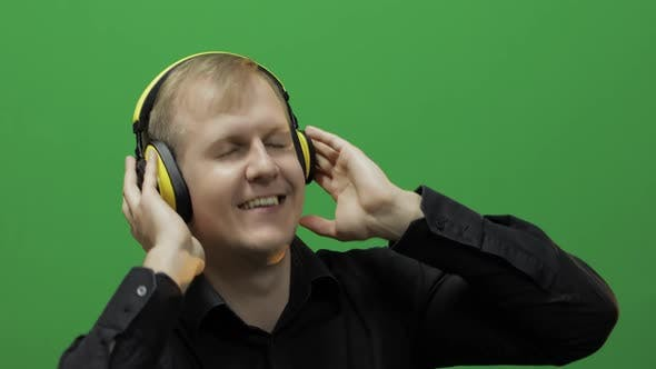 Thumbnail for Guy Listens To Music in Wireless Yellow Headphones and Dances