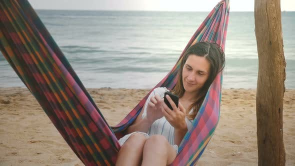 Thumbnail for Happy Relaxed Female Freelancer Lying in Hammock on a Beautiful Sea Coast Beach Using Smartphone