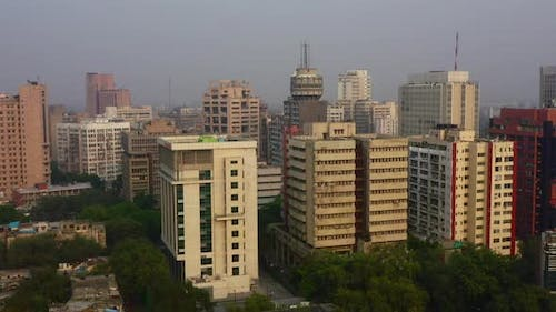 Slow Rising Aerial Pan of Tall Buildings in New Delhi on a Foggy Day