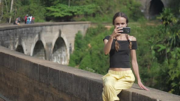Thumbnail for Girl in Black Top Makes Selfie Sitting on Bridge Barrier