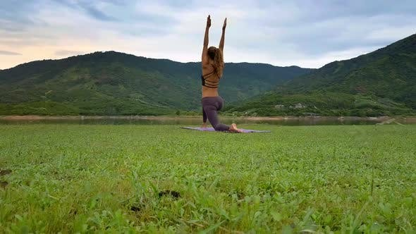 Cover Image for Side View Girl Raises Hands in Yoga Pose on Lake Bank