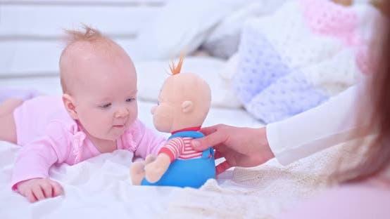 Schönes neugeborenes Baby liegt auf dem Bett und spielt mit einem Spielzeug. Neugeborenes Mädchen liegt auf ihrem Bauch und