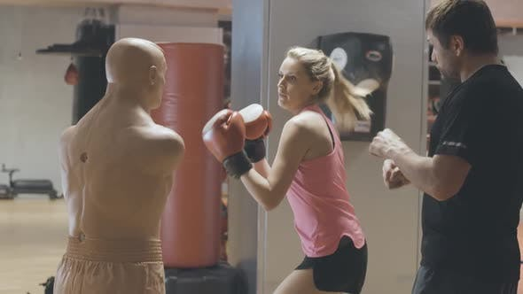 Blond Caucasian Woman in Boxing Gloves Punching Mannequin on Boxing Ring. Personal Trainer Training