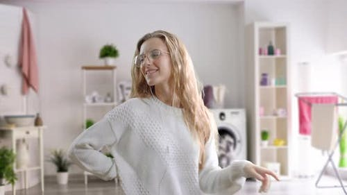 Happy Young Woman in Earphones Is Listening To Music with Smart Phone, Dancing and Smiling. The