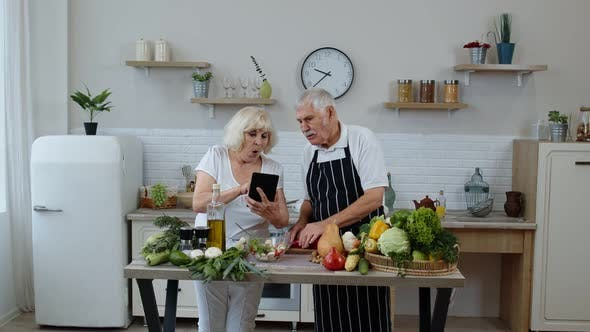 Thumbnail for Vegan Senior Grandparents Looking for a Culinary Recipe Online on Digital Tablet, Cooking Salad