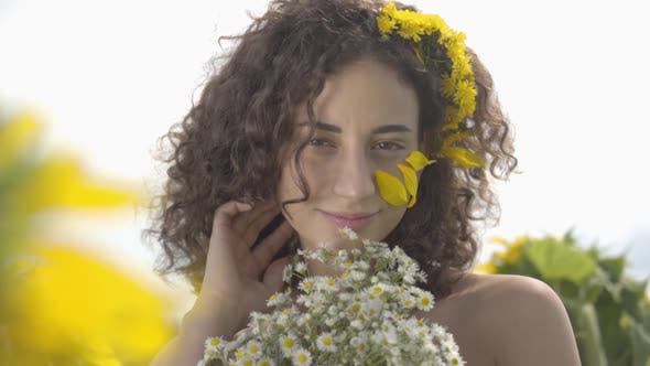 Thumbnail for Portrait of a Cute Curly Girl Looking at the Camera Smiling Standing in the Sunflower Field with