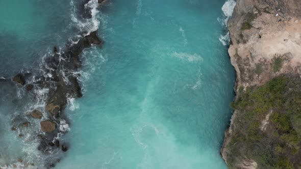 Thumbnail for Top down aerial view of waves breaking inside a small, rocky bay