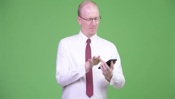 Thumbnail for Happy Mature Bald Businessman Using Phone